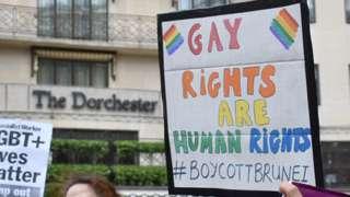 Protestors outside The Dorchester hotel on Park Lane, London