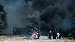 Palestinians burn tyres as they clash with Israeli forces near the border between the Gaza strip and Israel