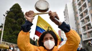 A demonstrator makes noise banging a pot during a protest against the government of President Ivan Duque on 4 May