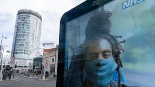 man with locs wearing face-mask on NHS poster
