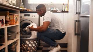 Homem botando roupa na máquina de lavar