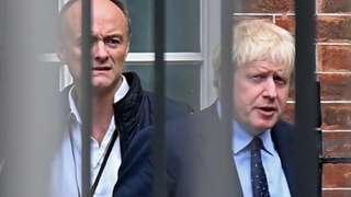 Dominic Cummings e Boris Johnson atrás de grade