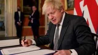 Boris Johnson signing the trade deal