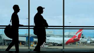 Passengers walk through an airport in Australia