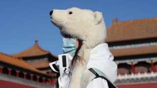 1月6日,一名游客戴着一顶熊形保暖帽参观北京故宫。