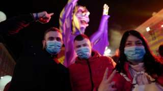 Revellers wear masks to protect themselves from the virus as they attend the Nice carnival on 25 February 2020