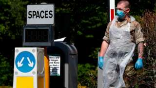 A soldier dressed in protective face mask and gloves waits at the entrance to a mobile coronavirus COVID-19 testing centre set up in a park and ride site in Salisbury.