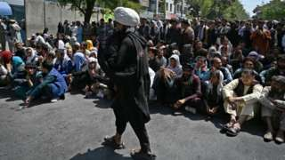 A Taliban fighter walks in front of people sitting along a road outside a bank waiting to withdraw money at Shar-e-Naw neighborhood in Kabul.