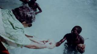 Пандит даје кокосов орах Сентинелцима приликом експедиције 1991. године