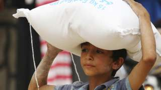"""A boy carries food aid given by UN""""s World Food Programme in Raqqa, Syria April 26, 2018"""