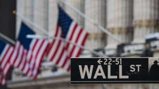 Wall Street sign in front of flags