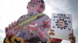 Manifestante segura cartaz com dizeres 'Fora Bolsovírus'
