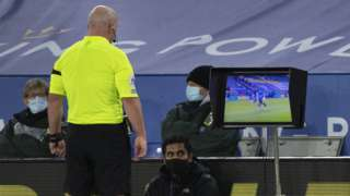 Referee Simon Hooper checks a TV monitor before awarding Fulham a penalty against Leicester