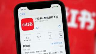 A mobile phone shows the APP interface of Xiaohongshu