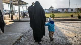 A woman and a child walk away