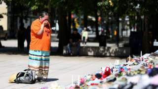 A woman mourns over 215 pairs of kids shoes outside Vancouver Art Gallery during a memorial on May 29, 2021 in Vancouver, British Columbia, Canada The remains of 215 children have been found buried at a Canadian residential school, an Indigenous band confirmed Thursday