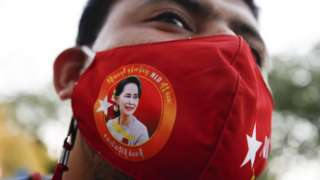 Protester wears a mask with Aung San Suu Kyi's face on it