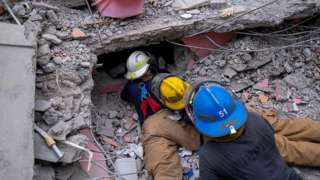 Haitian firefighters search for survivors, under the rubble of a destroyed hotel, in Les Cayes