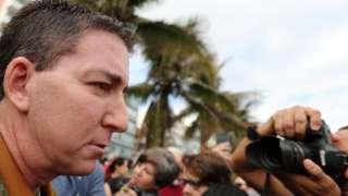 O jornalista Glenn Greenwald aparece de perfil durante manifestação no Rio de Janeiro, com fotógrafo no plano de fundo