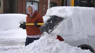 Image shows a woman in Chicago digging out her car after it was buried