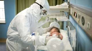 Doctor wearing PPE holding a baby