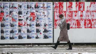 A woman walks past a wall with, on one side, the blue posters of the country's democratic party, and one the left, the red posters of the socialists
