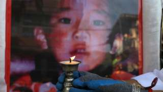 A woman holds a candle in front of a picture of the Panchen Lama to mark his 31st birthday in 2020