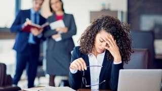 Mulher apoiando a cabeça na mão sobre mesa de escritório