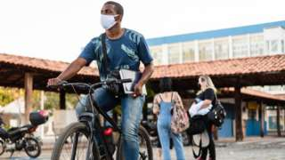 Homem anda de bicicleta segurando um caderno