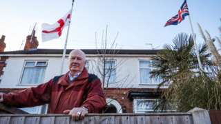 Ian with the Union Flag and the cCoss of St George in front of his house