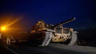 A Turkish tank drives towards the border with Syria near Akcakale