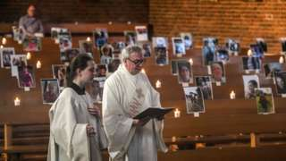 Deacon Bernd Malecki and server Anna hold an Easter service in front of portraits of believers at the St. Barbara church in Oberhausen, western Germany.