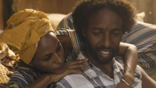 Still from film showing couple embracing