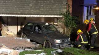 The car embedded in the wall of the house
