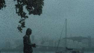 Atrás de janela molhada por pingos de chuva, homem é visto em pé em calçada na orla do Rio de Janeiro