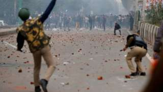 A riot police officer throws a piece of brick towards demonstrators during a protest against a new citizenship law in Seelampur, area of Delhi,