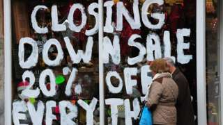 People walk past a store with the words 'Closing down sale 20% off everything' painted on the window