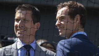 Tim Henman and Andy Murray smiling, dressed in suits, behind netting at Wimbledon