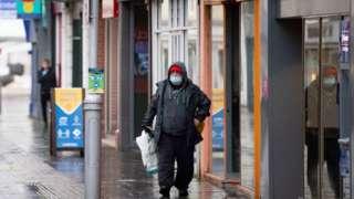 A man wears a face mask while walking through Bridgend town centre
