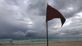View of an almost empty beach and a red flag before the arrival of the Hurricane Delta, in Cancun, in the state of Quintana Roo, Mexico, 06 October 2020
