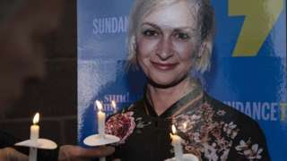 People hold candles in front of an image of Halyna Hutchins