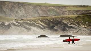 Surfers at a beach in Newquay, Cornwall