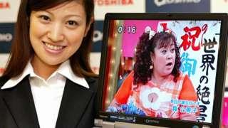 Seorang perempuan memegang laptop Toshiba 2004.