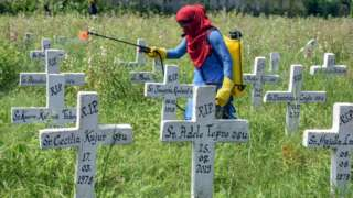 A municipal worker sanitises a Roman Catholic Church graveyard after the burial of Covid-19 coronavirus infected people