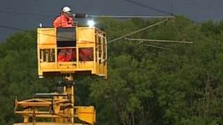 Engineers fixing overhead rail cables