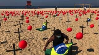 A demonstrator from the NGO 'Rio De Paz' ties a Brazilian flag to a cross in Copacabana beach on August 8, 2020 in Rio de Janeiro, Brazil.