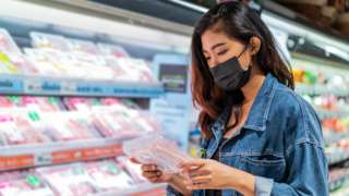 Woman buys meat in supermarket