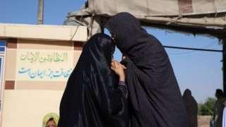 Duas mulheres de véu se cumprimentam em área aberta no Afeganistão