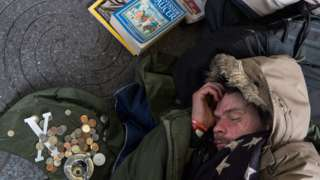 Homeless man sleeping by donations