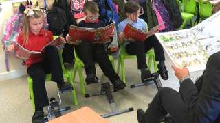 Teacher and three pupils using pedal machines at school